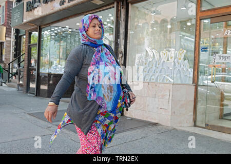 A woman in a colorful dress and head covering walks on 74th Street in Jackson Heights absorbed in her thoughts. Queens, New York City. - Stock Image