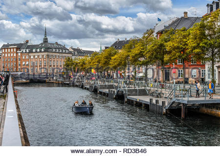 A group of people enjoy a canal cruise near Van Stranden and the historic center on an overcast Autumn day in Copenhagen, Denmark. - Stock Image