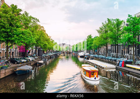 Channel in Amsterdam at sunset. Boat going down the river in Amsterdam. Picturesque cityscape of Amsterdam streets. - Stock Image