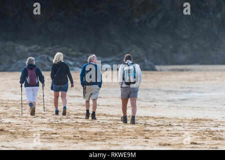 Walkers on Crantock Beach in Newquay in Cornwall. - Stock Image
