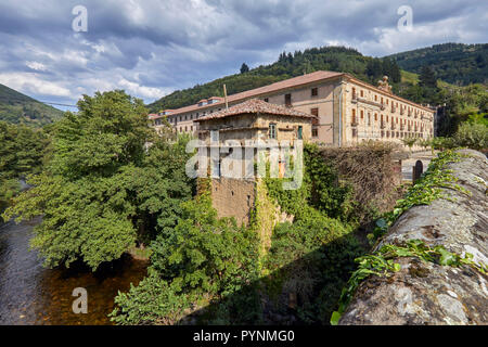 Monasterio de Corias (now a Parador) in the valley of the Río Narcea with terraced vineyards on the slopes - viewed from El Puente de Corias. Cangas d - Stock Image