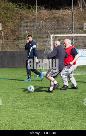 Middle-aged men taking part in a walking football session in Bolton, Lancashire, organised by the Bolton Wanderers - Stock Image
