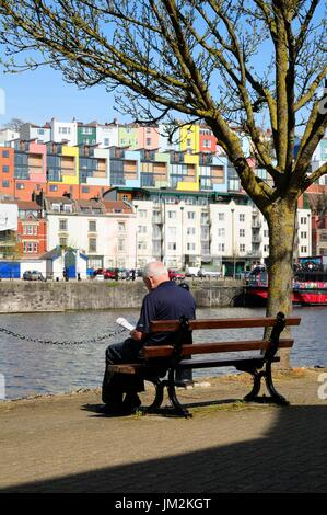 A older gentleman enjoying reading a book in pleasant sunshine on the waterfront of Bristol`s Harbourside. - Stock Image