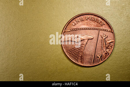 One penny English currency coin in a macro close-up on a rich luxurious golden background. Copyspace area for finance, - Stock Image