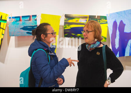 Huntington, New York, U.S. - March 1, 2014 -  At right, the wife of artist Thom O'Connor discusses his exhibit 'Hung Out To Dry' with a visitor at the Opening  Reception '3 Wild & Crazy Artists' at FotoFoto Gallery. - Stock Image