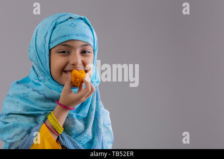 Young Muslim girl wearing hijab smiling and eating sweets - Stock Image