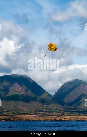 Tandem parasailers glide above the west coast of Maui. West Maui Mountains in the background. - Stock Image