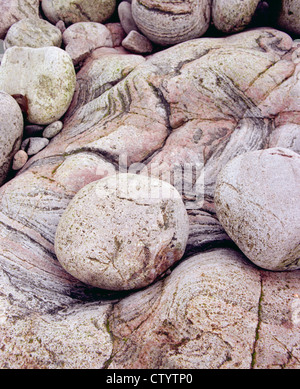 Rounded boulders scattered on the rocky coastline at Huisinish on the Isle of Harris - Stock Image