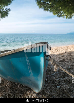 Small blue boat on the beach close to the sea on sunny summer day - Stock Image