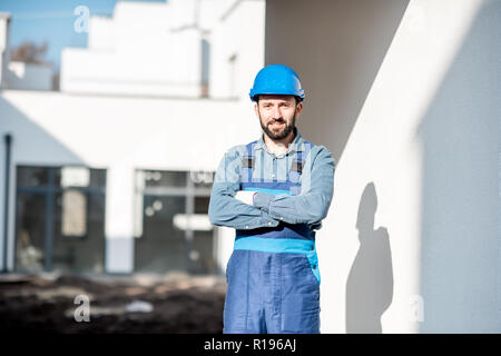 Portrait of a handsome builder in uniform on the construction site with white houses on the background - Stock Image