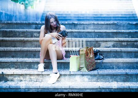 No money in wallet teenager girl is surprised to find the fact after extensive shopping spontaneous expressive expression - Stock Image