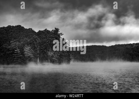 Early morning mist on mountain lake - Stock Image