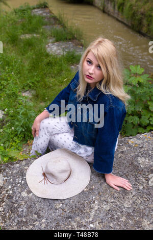 Young pretty blonde woman with vintage hat waiting on rustic bridge - Stock Image