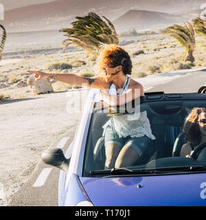 Happy blonde curly girl traveler on a convertible car standing and looking the beauty of the place around - lifestyle and travel vacation concept enjo - Stock Image