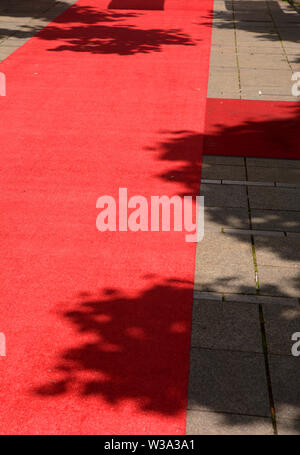 red carpet in the outdoor area in the midday sun, rolled out red carpet by day no people for an evening event - Stock Image