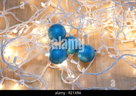 White holiday lights tangled up with four sparkly blue christmas balls - Stock Image
