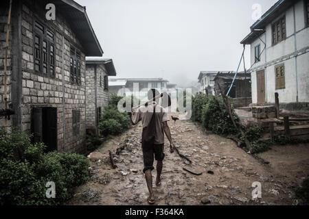 A farmer walks through a mountain village near Kalaw, Myanmar - Stock Image