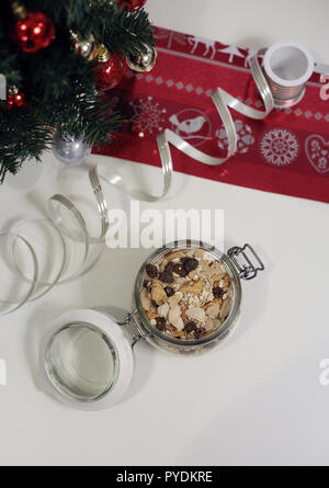 Homemade Christmas muesli in a glass jar. There is a Christmas tree and other decorations in the background. Merry Xmas! - Stock Image