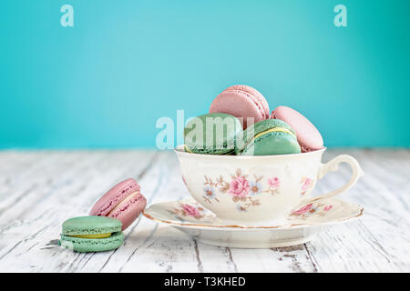 Antique Bavaria Winterling footed tea cup from the 1950s' filled with pink strawberry and green tea macarons on a rustic white table against a teal ba - Stock Image