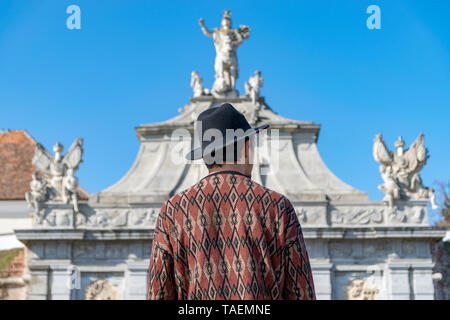 A tourist young man with a hat admiring a fortress gate entrance. A man admiring the 3rd Gate of the Alba-Carolina Fortress in Alba Iulia, Romania. Al - Stock Image