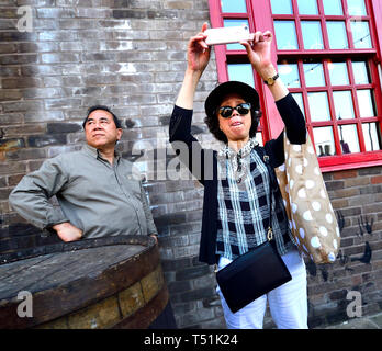 London, England, UK. Japanese woman taking a photo with her mobile phone in Southwark - Stock Image