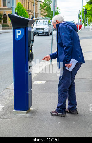 An elderly man trying to work out how to operate a newly installed solar powered parking meter in Hobart, Tasmania - Stock Image