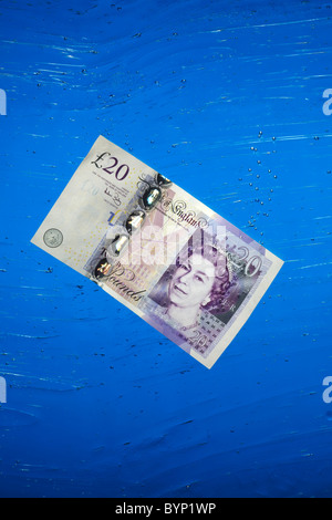 Twenty Pound Note sinking in  Water - Stock Image