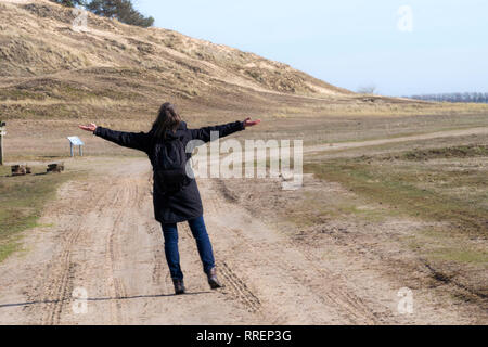 Stock Photo of Caucasian woman in black coat arms raised on empty road towards sunset horizontal - Stock Image