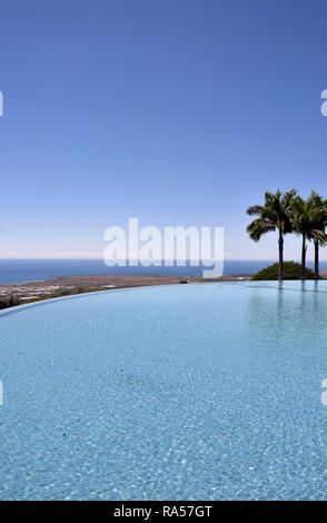 Blue water from infinity pool overlooking tropical coast in Hawaii - Stock Image