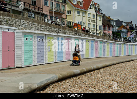 Young woman pushing child in pushchair on the seafront of Lyme Regis, UK; row ow pastel coloured beach huts in the background. - Stock Image