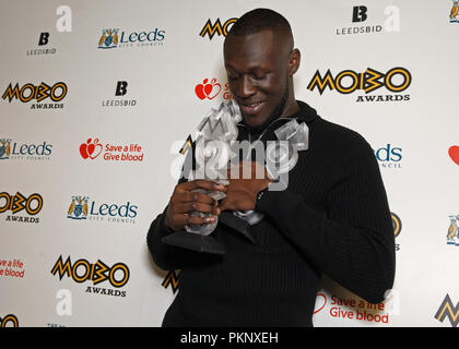 Stormzy at the 2017 MOBO Awards on 29 November 2017. Stormzy is holding his three MOBO Awards trophies, for Best Album (Gang Signs & Prayer), Best Male Act and Best Grime Act. - Stock Image