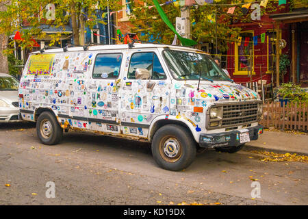Van covered in stickers parked along street in Kensington Market in downtown, Toronto, Ontario, Canada - Stock Image