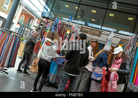 People shopping for scarves at a scarf stall 'Kashimi Scarves' in Spitalfields Market near Brick Lane in East London E1 UK  KATHY DEWITT - Stock Image