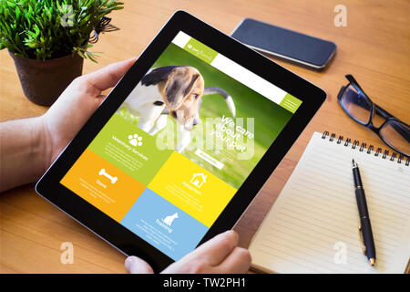 hands of a man holding a pet website device over a wooden workspace table. All screen graphics are made up. - Stock Image