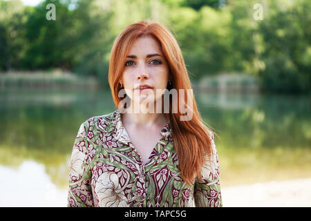 cool and confident young woman wearing floral pattern summer dress with long red hair standing by lake - authentic real people - Stock Image