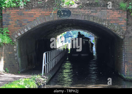 Silhouetted rear view of narrowboat on a UK canal moving away through a dark canal tunnel; people on towpath watching at other end in bright sunlight. - Stock Image