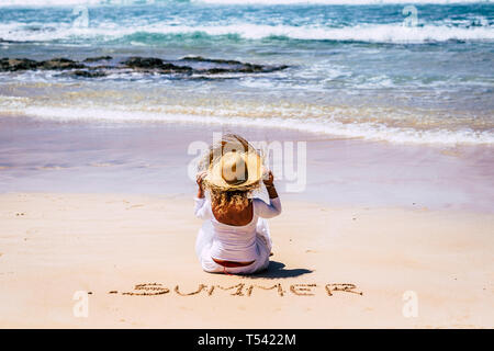 Summer vacation holiday concept with people - white dress tourist woman sit down at the beach on the sand looking the blue waves from sea and holding  - Stock Image