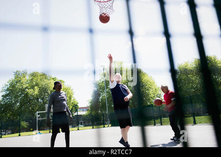 Active senior men playing basketball in sunny park - Stock Image