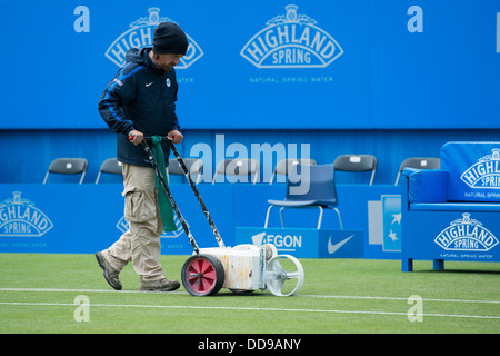 Groundsman paints the white lines on a grass tennis court with a machine - Stock Image