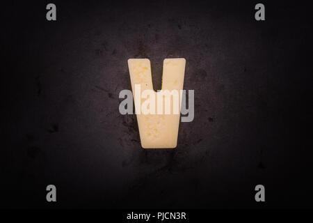 Butter Forms V on cast iron skillet background - Stock Image