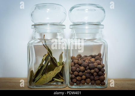 Bay leaves and allspice in a glass jar on the wooden shelf - Stock Image