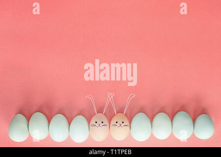 Decorated Easter eggs with cute bunny face and ears drawn on over a pastel background with room for copy space. Image shot from top view. - Stock Image