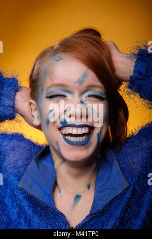 Happy, pretty, redheaded, young woman with crazy make-up smiling - Stock Image
