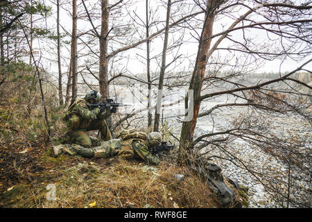 Norwegian Rapid reaction special forces FSK soldiers scouting in the forest trees. - Stock Image