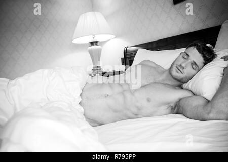 Good looking man with muscular body and six pack abs sleeping in between white sheets in hotel room - Stock Image