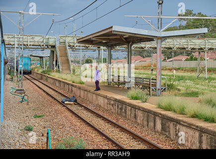 Train leaves unknown station as station attendant looks on while the Premier Classe train stopped in the Free State South Africa, January 17, 2019 - Stock Image