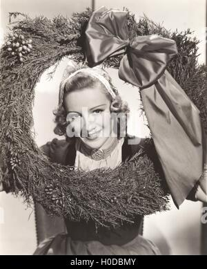 Woman holding large Christmas wreath with bow - Stock Image