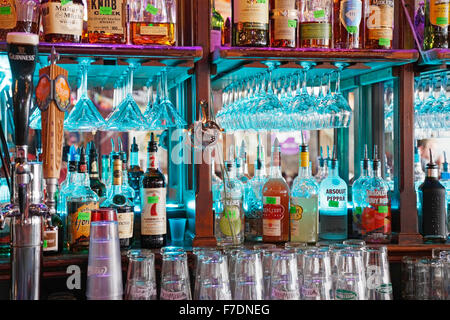 Alcohol and liquor bottles lined up in a bar and pub - Stock Image