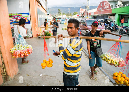Timorese men, street vending fruits and vegetables hanging on ropes from neck yokes made of sticks on a busy market street of capital Dili, East Timor. - Stock Image