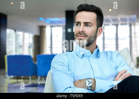 Businessman sitting on sofa with arms crossed - Stock Image